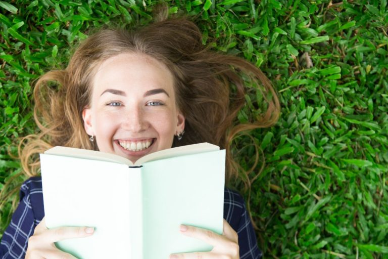 Birželio renginiai bibliotekoje. Mergina skaitanti ant žolės.