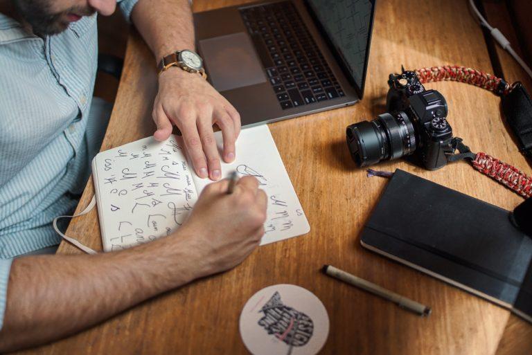 Įgūdžių laboratorijos iliustracija. Vaikinas sėdintis prie darbo stalo, rašantis.