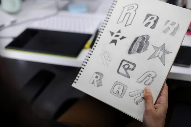 Ranka, laikanti sąsiuvinį, kuriame nupiešti įvairūs logotipai