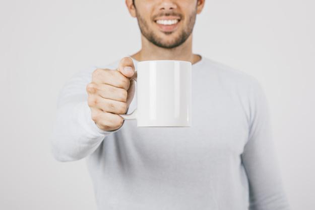 Vyras rankoje laiko puodelį