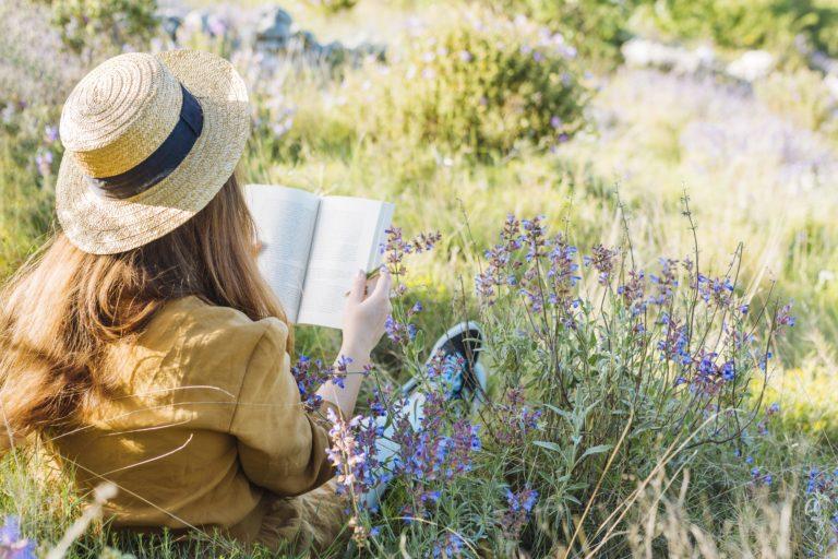 Moteris skaito knygą pievoje