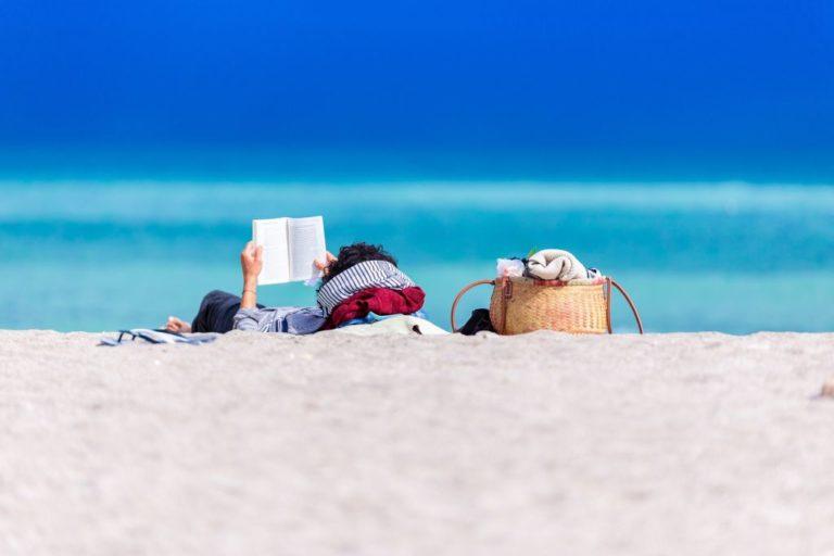 Moteris guli ant smėlio prie jūros ir skaito knygą