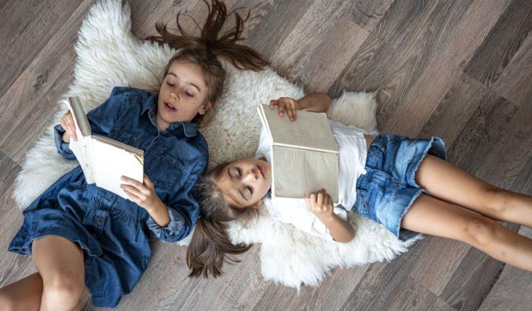 Dvi mielos mergaitės skaito knygas gulėdamos ant grindų namuose